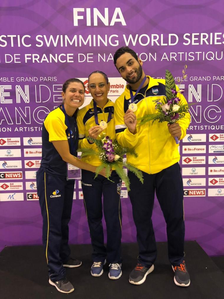 Giovana Stephan e Renan Alcântara recebem o ouro ao lado da técnica Roberta Perillier